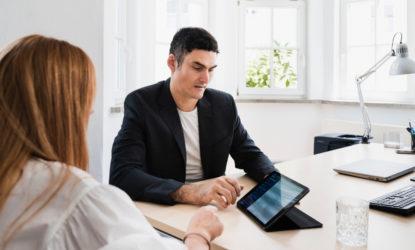 Christian und Julia besprechen etwas an einem Tisch mit einem Tablet