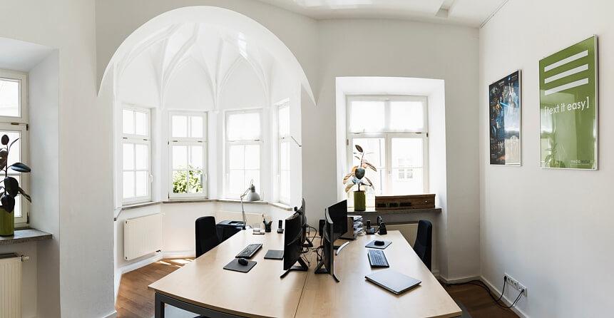 Zwei nebeneinanderstehende Schreibtische im Büro von Mediatextur